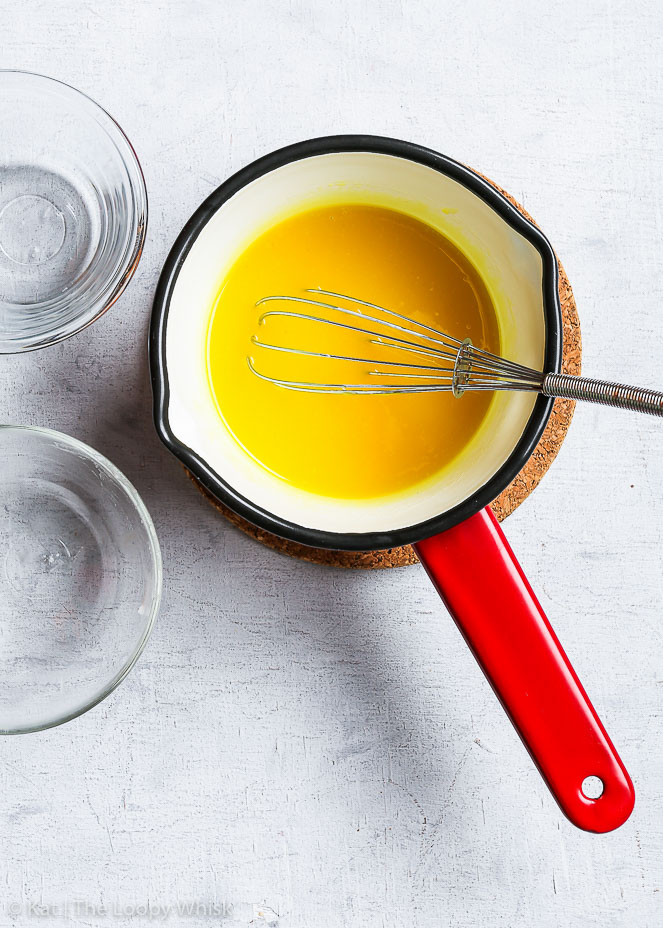 Bird's-eye view of the final product: the golden yellow vegan lemon curd is in a pretty red saucepan with a whisk in it.