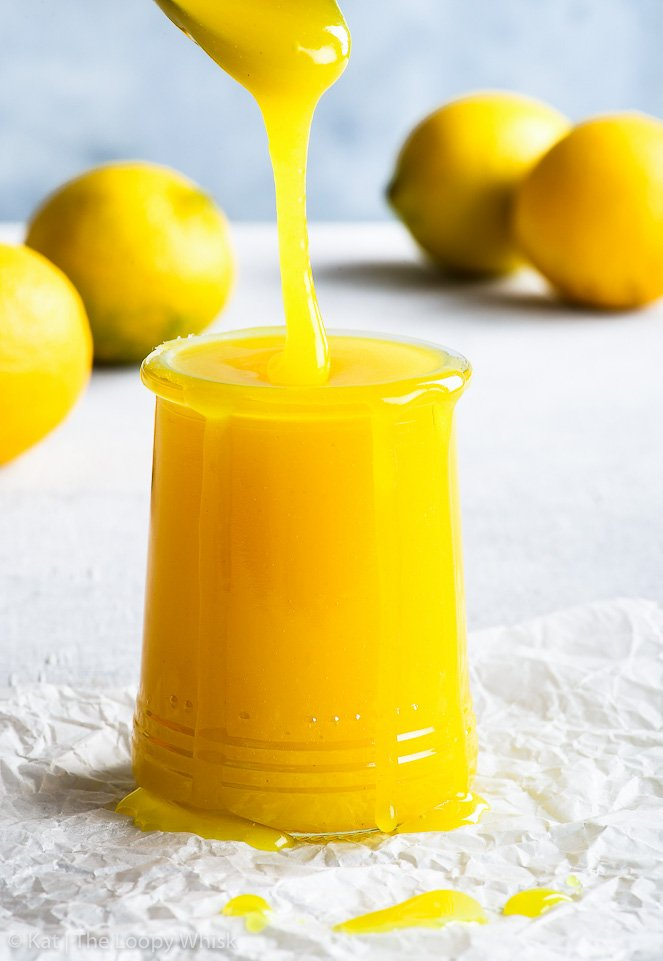 Golden yellow vegan lemon curd is being drizzled into a pretty glass jar from a spoon. Some lemons are in the background.