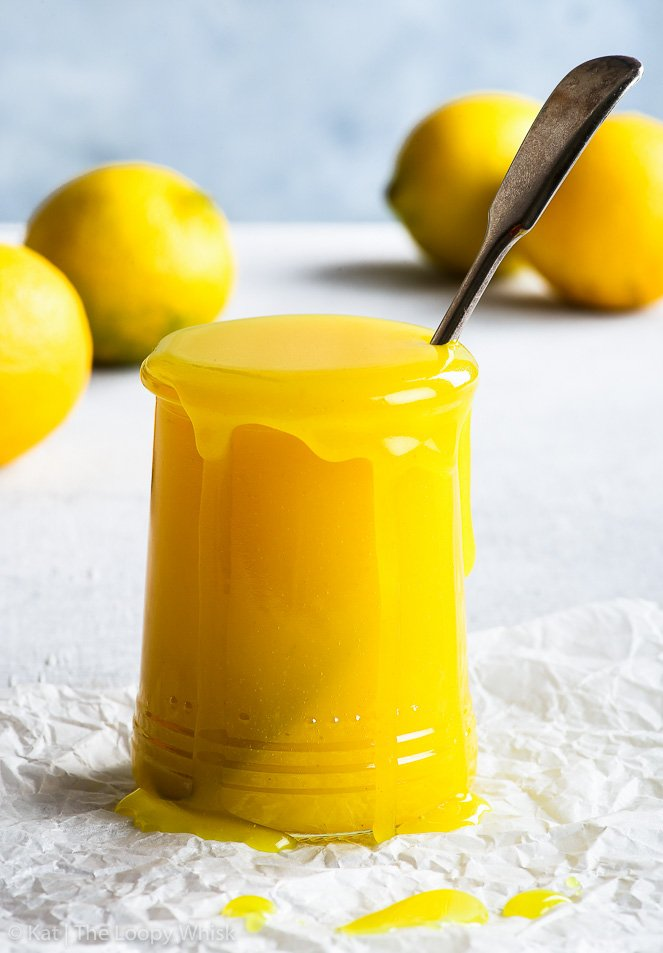 A glass jar full of the golden yellow vegan lemon curd, with a metal spoon in the jar. Some lemons are in the background.