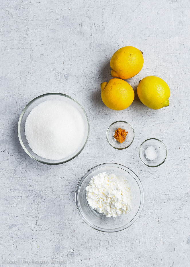Bird's-eye view of the vegan lemon curd ingredients: lemons, sugar, cornstarch, pinch of salt and turmeric.
