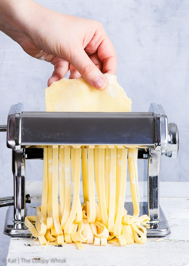The process of cutting up a gluten free pasta sheet into tagliatelle, using a pasta machine, on a white surface with a blueish grey background.