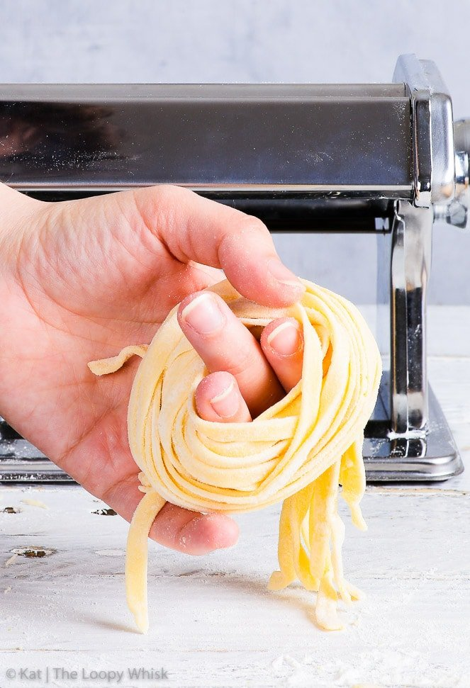 The process of rolling up the gluten free tagliatelle into a nest by hand, in front of the pasta machine on a white wooden surface.