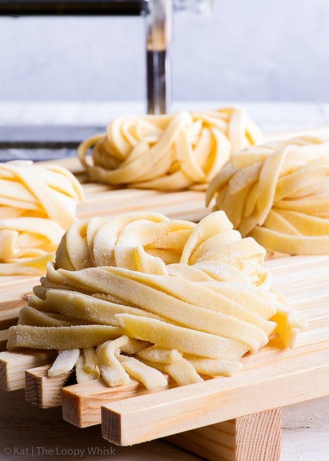 Nests of homemade gluten free pasta, in the shape of tagliatelle, on a wooden drying or cooling rack.