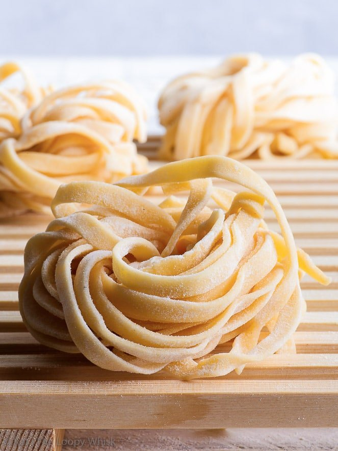 Dried nests of homemade gluten free pasta, in the shape of tagliatelle, on a wooden drying or cooling rack.