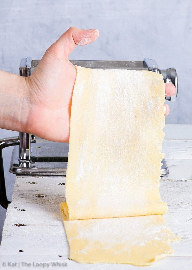 A smooth, generously floured gluten free pasta sheet held in a hand, in front of the pasta machine on a white surface in front of a blueish grey background.