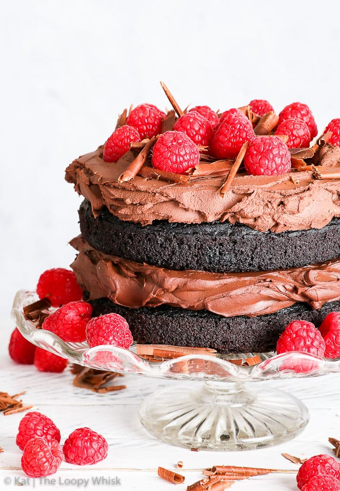 Close-up of the gluten free vegan chocolate cake on a decorative glass cake stand, on a white surface with white background. Raspberries decorate the top of the cake, and are also positioned around the cake on the cake stand, and around the stand itself. Chocolate shavings complete the slightly rusting, beautiful vegan cake.