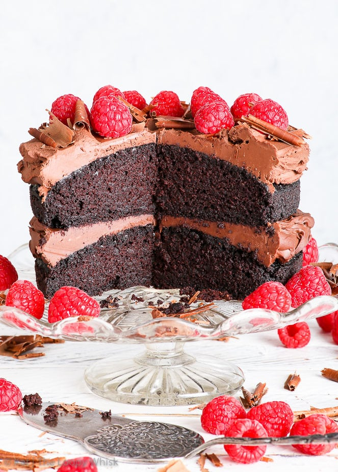 Gluten free vegan chocolate cake on a decorative glass cake stand, on a white surface with white background. Raspberries decorate the top of the cake, and are also positioned around the cake on the cake stand, and around the stand itself. Chocolate shavings complete the slightly rusting, beautiful vegan cake. A few pieces of the cake have been cut out, exposing it's moist, chocolatey interior.