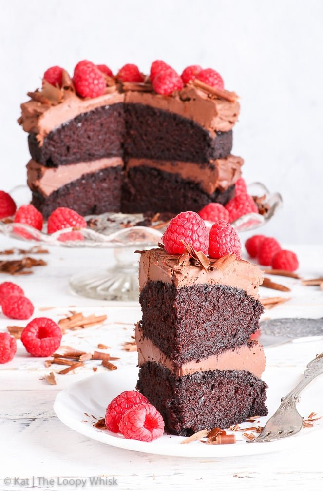 A piece of the gluten free vegan chocolate cake is in the foreground, on a white plate with an antique dessert fork. The rest of the cake on a glass cake stand is in the background.