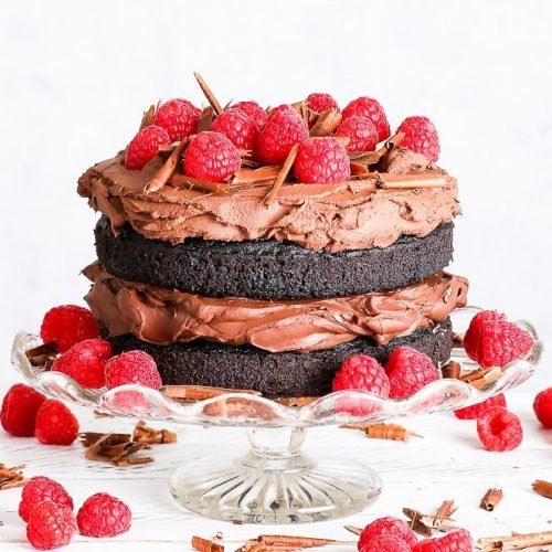 Gluten free vegan chocolate cake on a decorative glass cake stand, on a white surface with white background. Raspberries decorate the top of the cake, and are also positioned around the cake on the cake stand, and around the stand itself. Chocolate shavings complete the slightly rusting, beautiful vegan cake.