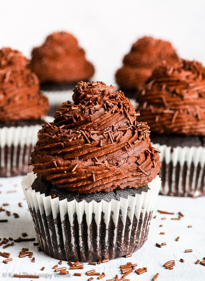 A gluten free vegan chocolate cupcake is in the foreground, with more gluten free vegan cupcakes in the background. The surface and background are very light, almost white, with extra dark chocolate sprinkles on the surface.
