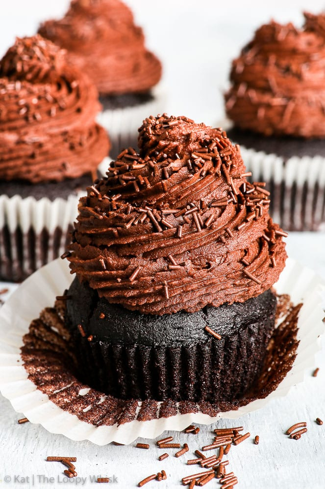 A gluten free vegan chocolate cupcake with partially removed cupcake liner is in the foreground, with more gluten free vegan cupcakes in the background. The surface and background are very light, almost white, with extra dark chocolate sprinkles on the surface.
