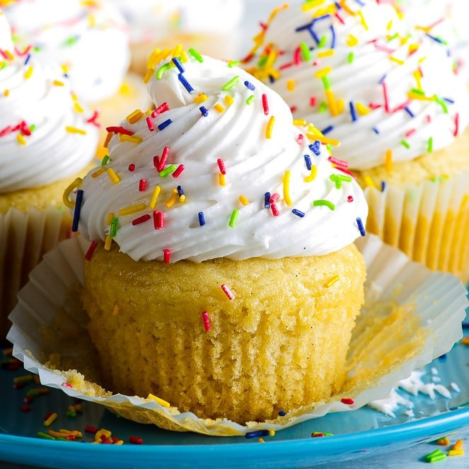 Gluten free vegan vanilla cupcakes in plain white cupcake liners on a blue plate. They are decorated with swirls of vegan vanilla frosting and colourful sprinkles. The cupcake in the front has had its cupcake liner partially removed.