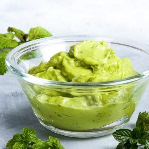 Creamy vibrant green healthy avocado pesto in a small glass bowl on a light blueish grey surface. A few mint sprigs are sprinkled around it.