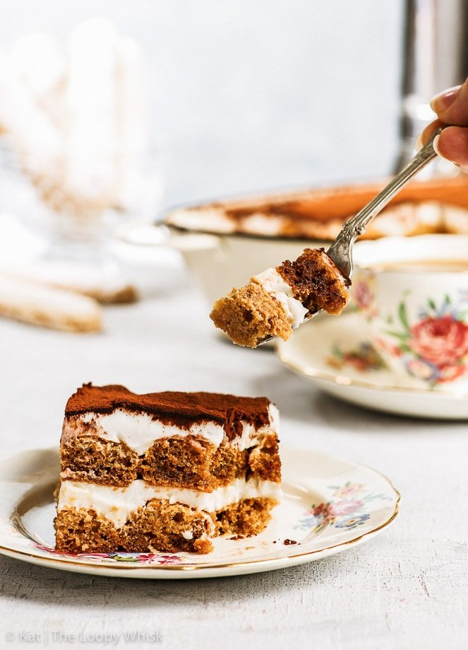 A slice of dairy and gluten free tiramisu on a decorative antique plate. A bite is being taken out of it. The dish with the rest of the tiramisu, a cup of coffee and more homemade gluten free ladyfingers are in the background.