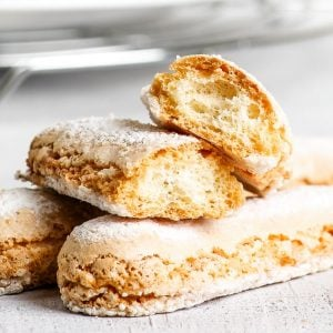 The perfect gluten free ladyfingers arranged in a small pile in the forefront. One ladyfinger cookie has been broken in half, exposing its airy, dry texture.