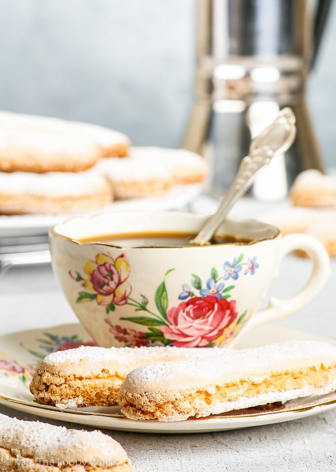 The perfect gluten free ladyfingers as part of an elegant arrangement. Two ladyfinger cookies are on a decorative antique coffee saucer also holding a cup of coffee. More gluten free sponge fingers and a cafetiere are in the background.