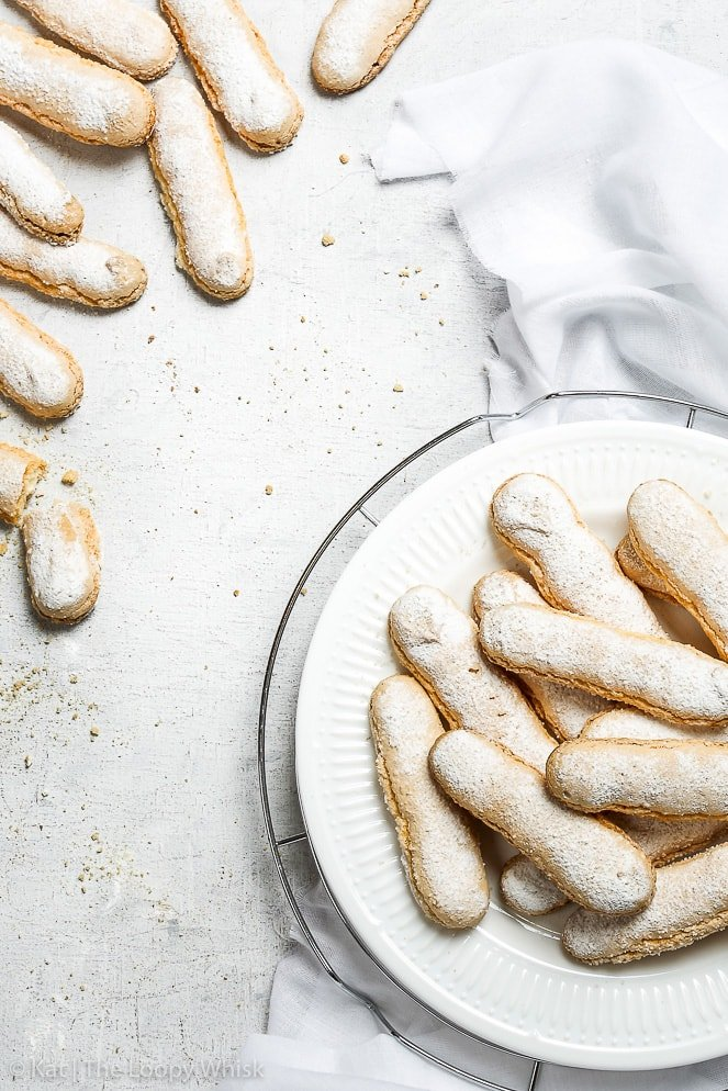 The perfect gluten free ladyfingers, an overhead view on a white surface. Some of the gluten free sponge fingers are arranged on a white plate on top of a metal cooling rack, some are scattered on the white wooden surface.