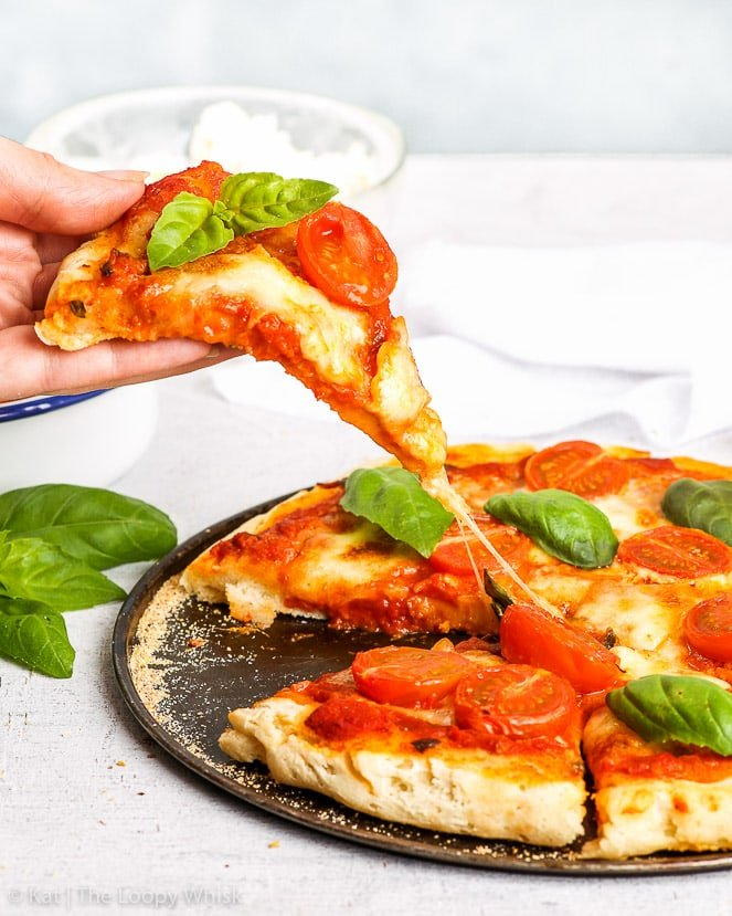 A piece of the best gluten free pizza is being lifted from the plate with the whole pizza: the cheese is delightfully stringy.