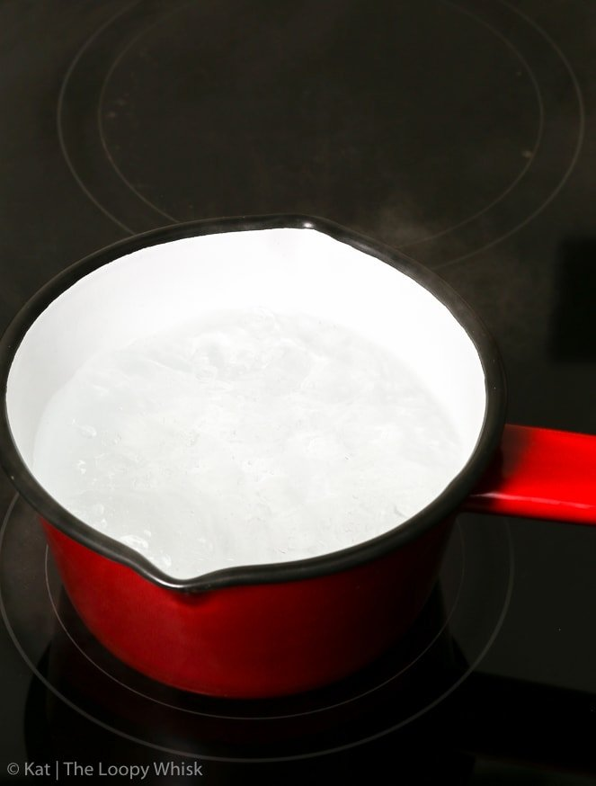 Bringing a small red saucepan filled with water to a boil, as part of the blanching almonds process.