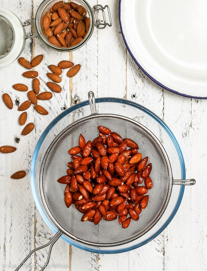 The quickly boiled almonds being drained above a glass bowl on a white wooden surface.