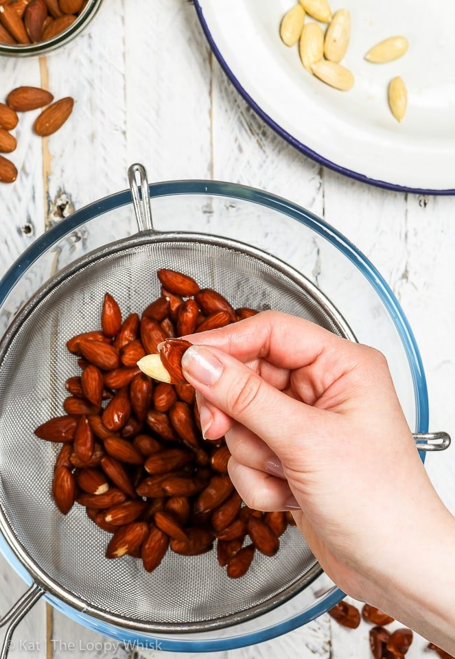 How to blanch almonds: after draining the almonds, squeezing each almond removes its skin.