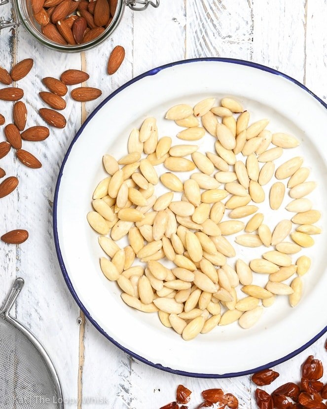 Blanched almonds on a white plate on a white wooden background.