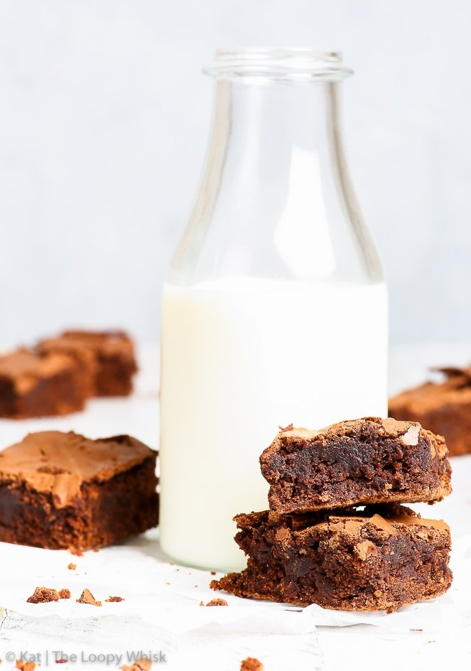 Fudgy, gooey gluten free brownies are arranged around a half-filled milk bottle on a white wooden surface in front of a greyish blue background.