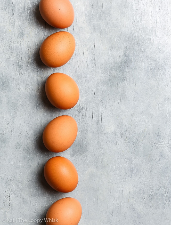 An overhead shot of six brownish orange eggs in a row, on a grey background.