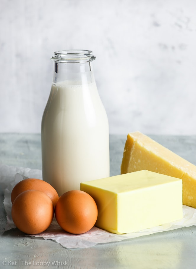 Commonly grouped together: a bottle of milk, a block of butter, (parmesan) cheese and eggs. On a grey surface with a light greyish white background.