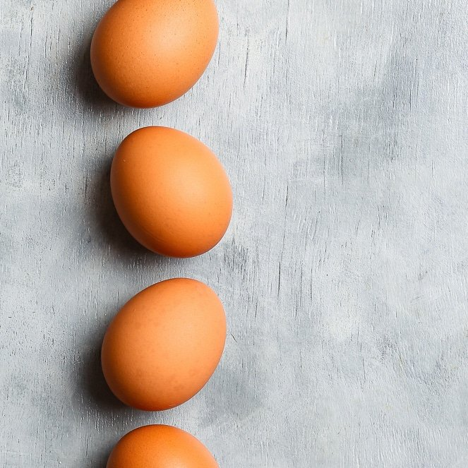 An overhead shot of four brownish orange eggs in a row, on a grey background.