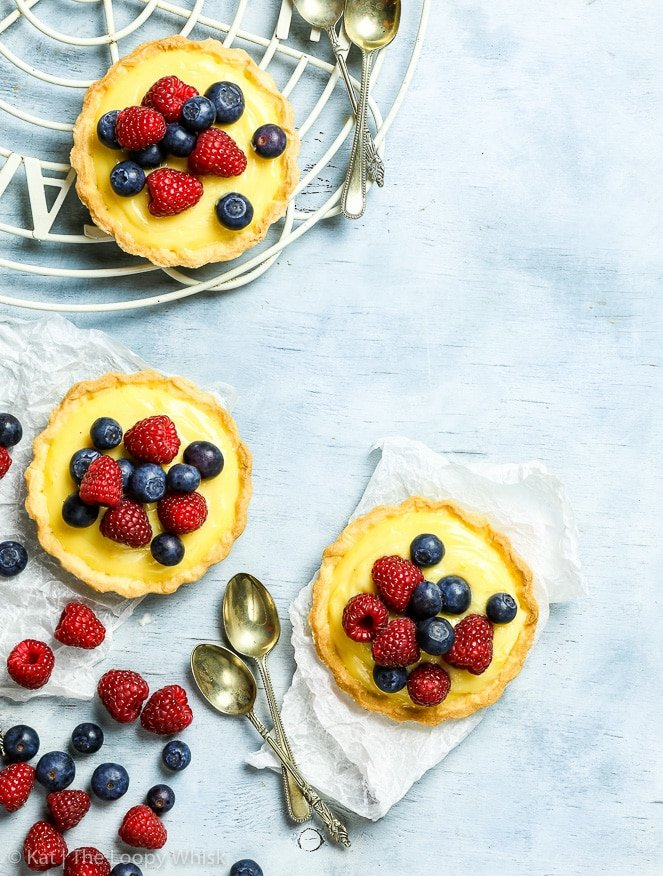 Overhead shot of three gluten free berry tartlets. All three tarlets are filled with a golden yellow lemon cream and topped with raspberries and blueberries. A few antique dessert spoons are arranged around the tartlets.