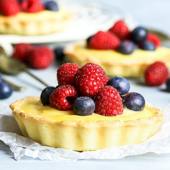 A gluten free tartlet filled with a golden yellow lemon cream and topped with a mixture of raspberries and blueberries, on a slightly crumpled piece of white parchment paper. More gluten free berry tartlets are in the background.