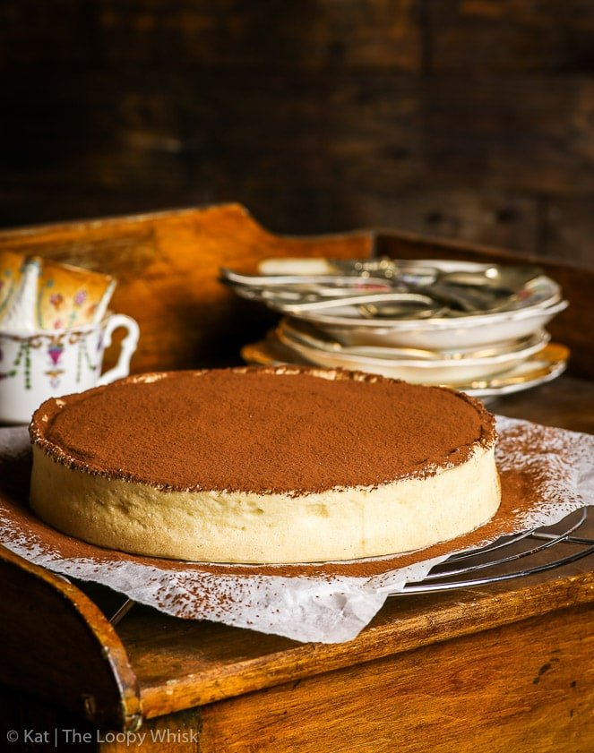 The gluten free chocolate tart on a small wooden serving table. The top of the tart has been dusted with cocoa powder. A pile of antique dessert plates and some cups are in the background.