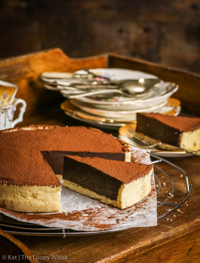 The gluten free chocolate tart on a small serving table. Two pieces of the tart have been cut. A pile of antique dessert plates and some cups are in the background.