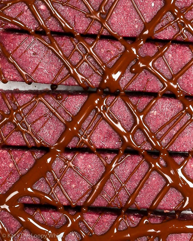 Chocolate raspberry energy bars, a close-up. The pink-violet healthy energy bars are drizzled with dark chocolate.