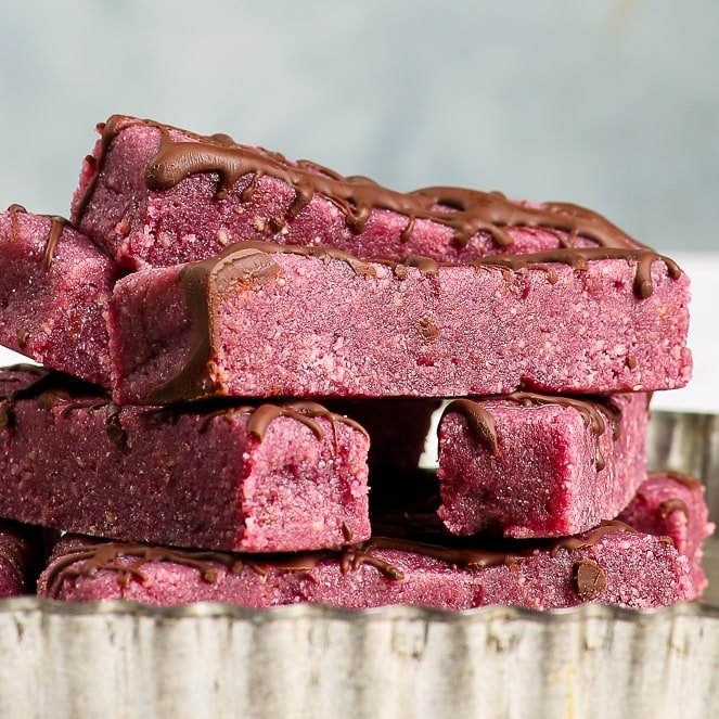 Chocolate raspberry energy bars in a stack on an antique metal tray, on a white surface in front of a greyish blue background.