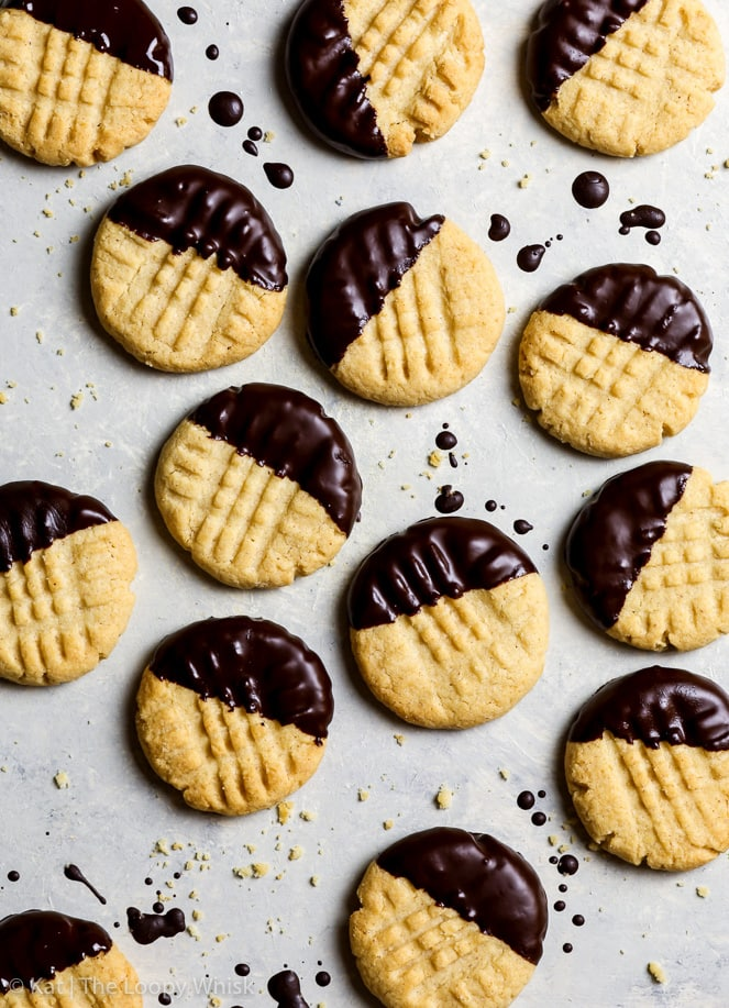 Overhead shot of gluten free peanut butter cookies dipped in dark chocolate on a greyish white background. A few crumbs and splatters of chocolate complete the scene.