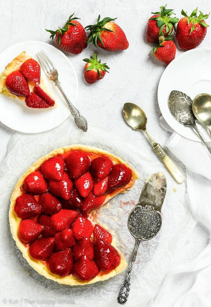 Overhead view of the gluten free strawberry tart on a vintage white cooling rack on a white background. A large piece of the tart has been cut. The strawberries arranged on top of the tart are a vibrant red and glossy from the jam glaze. An antique cake server, a white plate with a piece of the tart and antique dessert spoons are next to the tart, as well as a few whole and halved strawberries.