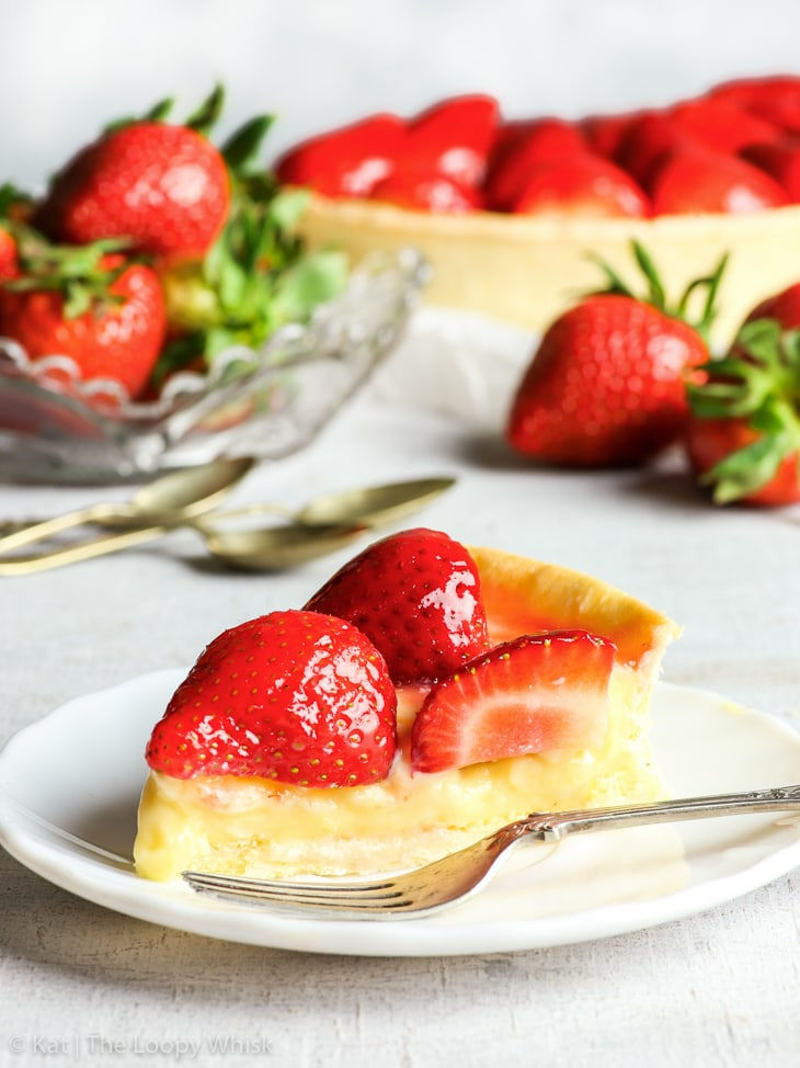 Side view of a piece of the gluten free strawberry tart on a white dessert plate with an antique dessert fork. The pastry shell is thin, the vanilla pastry cream a pastel yellow colour, and the strawberries are vibrantly red and shiny from the jam glaze. The rest of the tart as well as more strawberries are in the background.