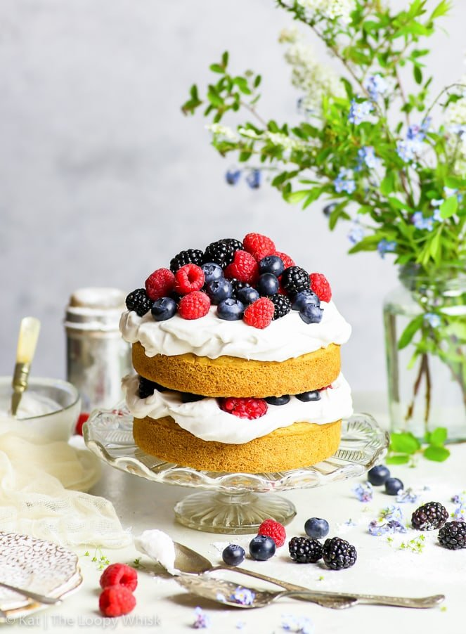 The gluten free vegan vanilla cake with a small heap of summer berries on top of it is on a glass cake stand, on a white surface in front of a greyish background. A vase with green branches and forget-me-nots is in the background. A few berries and spoons are scattered about the cake stand.