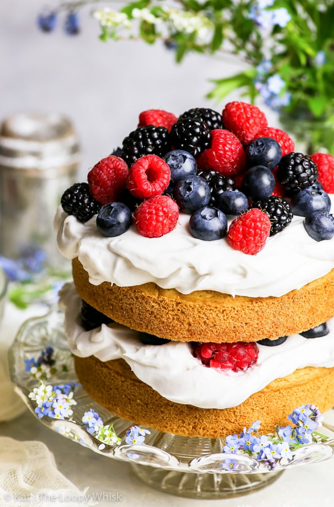 A close-up of the gluten free vegan vanilla cake with a small heap of summer berries on top of it – raspberries, blueberries and blackberries.