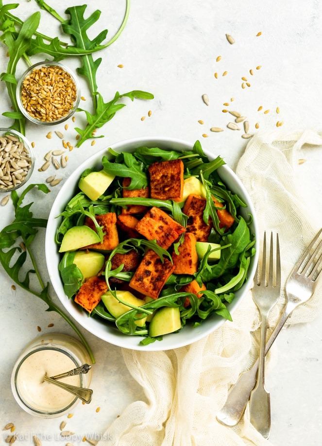 Overhead shot of the vibrant sweet potato & arugula salad with avocados in a white ceramic bowl. Two forks and a beige napkin are next to the bowl. Linseeds and sunflower seeds are sprinkled around the surface, along with a few arugula leaves.