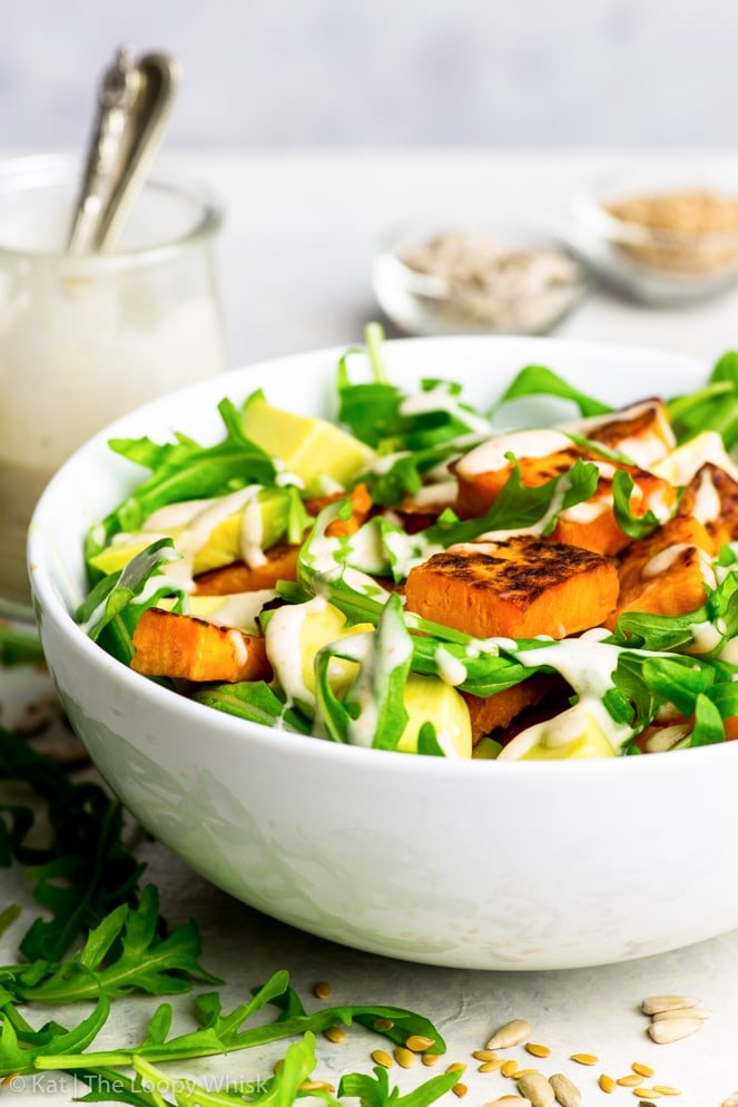 Close-up of the vibrant sweet potato & arugula salad with avocados, drizzled with the creamy peanut butter dressing in a white ceramic bowl.