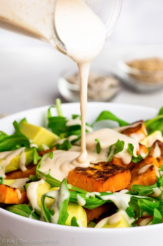 Close-up of the peanut butter salad dressing being pored onto the vibrant sweet potato & arugula salad.