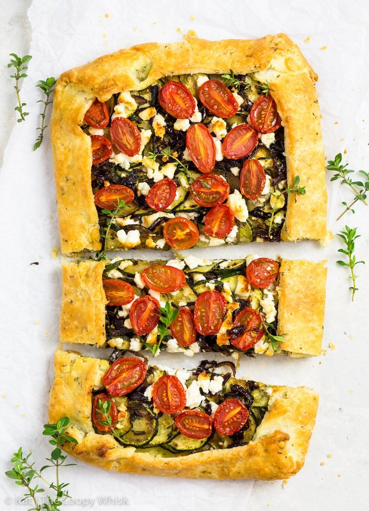 Overhead shot of the rectangular gluten free zucchini galette on a white background with a few thyme sprigs sprinkled around it. The galette has been cut into three pieces.