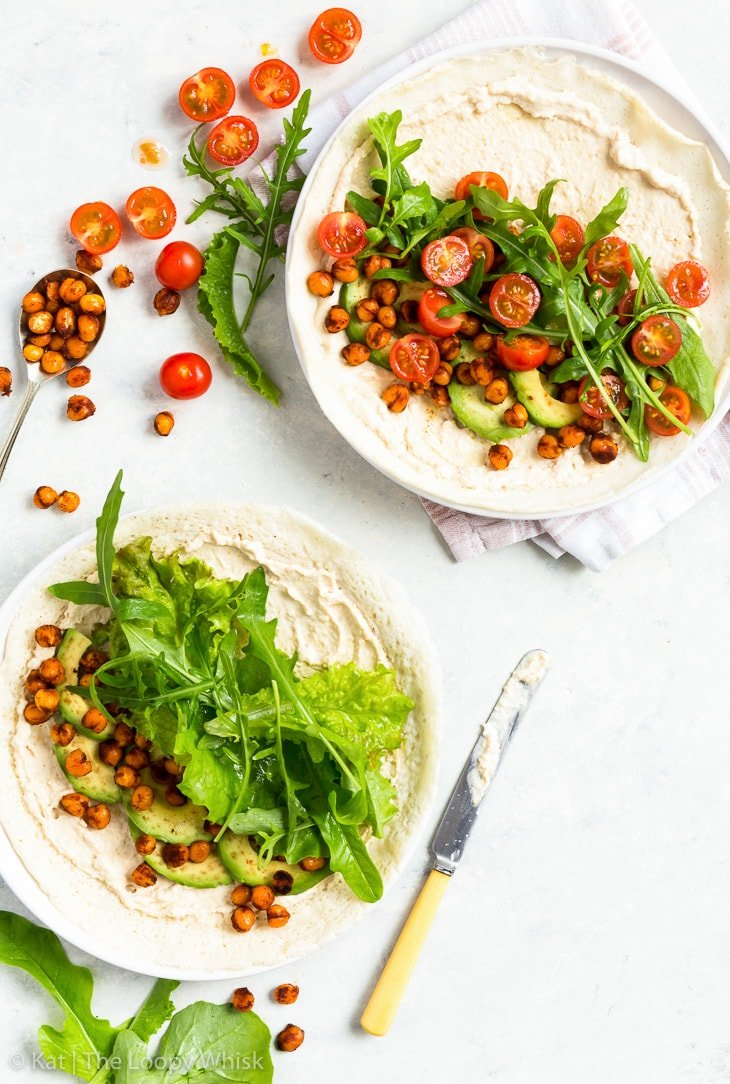 Overhead view of two gluten free veggie wraps, not rolled up yet. Hummus has been spread on them, and sliced avocado, halved cherry tomatoes, salad leaves and spicy chickpeas arranged on top. The plates with the wraps sit on a light backdrop. A knife with a bit of hummus smeared on it, and a spoon holding more roasted spicy chickpeas are next to the plates.