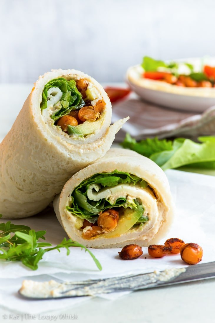 Rolled-up gluten free veggie wrap cut in half, filled with vibrant green salad leaves, creamy avocado and spicy chickpeas. The wrap is on a piece of parchment paper, with a few salad leaves and salad leaves lying around.