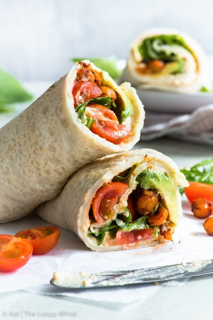Rolled-up gluten free veggie wrap cut in half, filled with vibrant red cherry tomatoes, green salad leaves, creamy avocado and spicy chickpeas. The wrap is on a piece of parchment paper, with a few halved cherry tomatoes and salad leaves lying around.