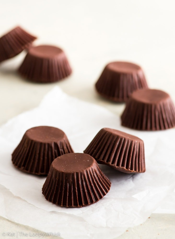 Homemade peanut butter cups on a white backdrop. Three cups with their dark brown chocolate shells are in the foreground on a piece of parchment paper.