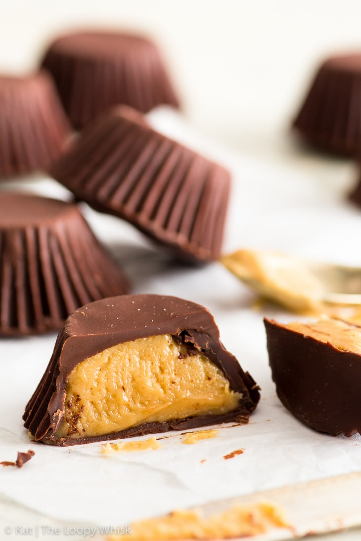 Homemade peanut butter cups on a white backdrop. One cup is in the foreground, cut in half with a knife that's lying in front of it. The fudgy golden brown peanut butter filling is exposed.